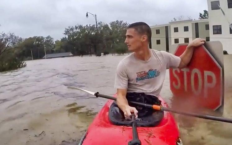 Man Kayaks Through Flooded Roads